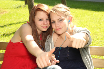 thumbs up - teenager girls sharing music