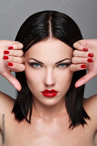 Portrait of  woman with make-up and red bright manicure