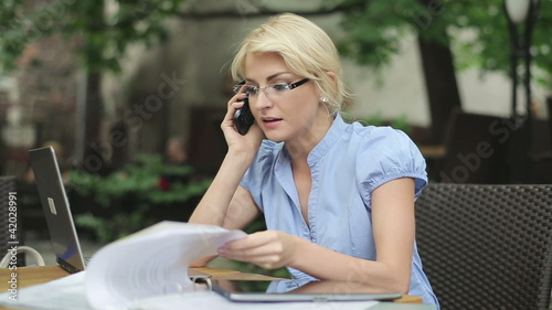 Busy multitasking attractive businesswoman in cafe