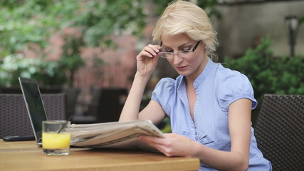 Happy businesswoman reading newspaper in cafe, steadicam shot