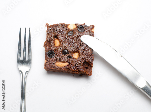 Piece of brownie with fork and knife on white isolated backgroun