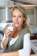 Portrait of blond woman drinking milk in home kitchen