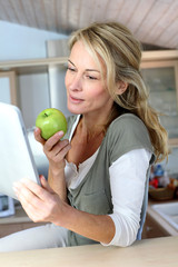 Cheerful adult woman websurfing with tablet and eating apple