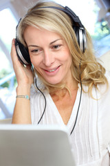 Middle-aged blond woman listening to music with tablet
