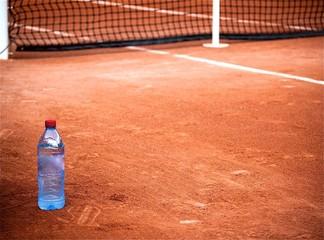 Bouteille d'eau et terrain de tennis