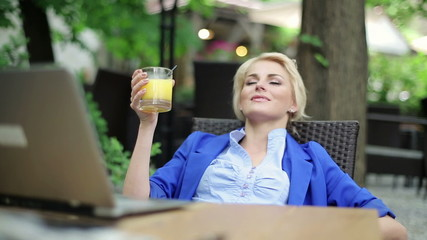 Businesswoman relaxing and drinking drink in cafe