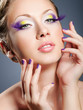 Woman face with bright violet makeup and manicure
