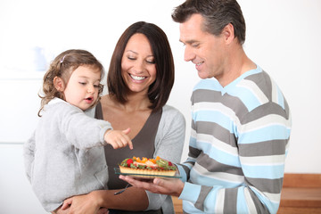 Parents preparing a bite to eat for little girl