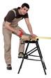Male carpenter sawing.