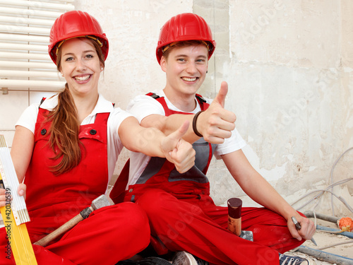 Worker in a building lot fixing up a house show thumbs up
