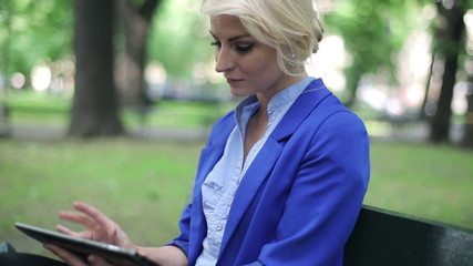 Young businesswoman working on tablet computer in park