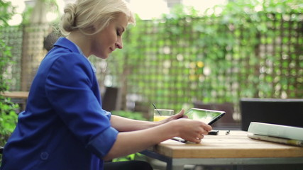 Young businesswoman working on tablet computer in cafe