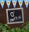 Tafel mit O zapft is auf Holzbrett mit Efeu und Wimpeln