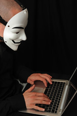 member of the Anonymous hacker group in front of the laptop