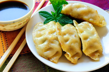 A Plate of Fried Chinese Gyoza, Soy Sauce and White Chopsticks