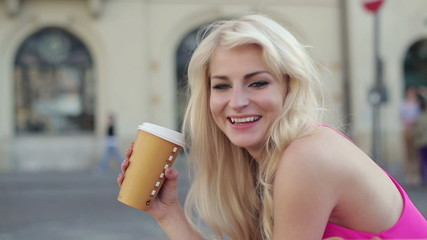 Young attractive woman drinking coffee in city