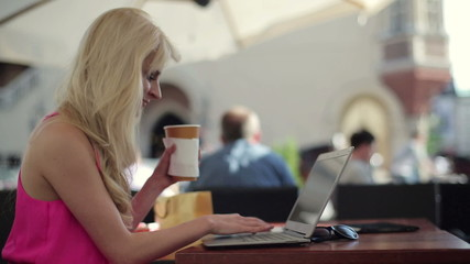 Attractive woman with laptop in cafe, steadicam shot