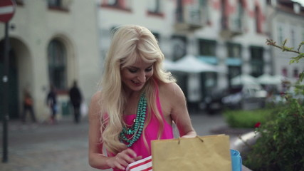 Happy woman with shoping bags in city, steadicam shot
