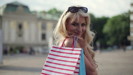 Happy woman with shoping bags in the city, steadicam shot