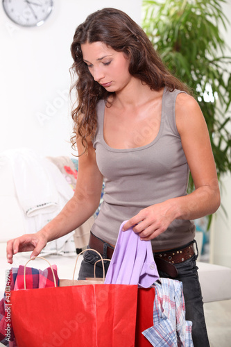 Woman searching through shopping bags