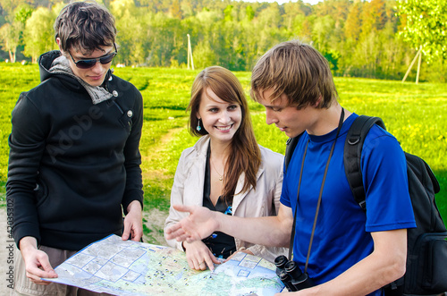 Three friends traveling, they look at a map