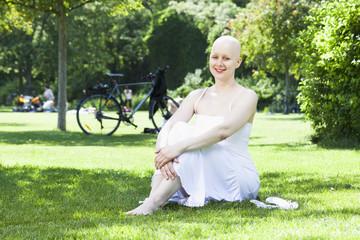 Frau mit Glatze im Park