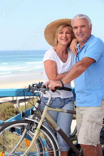 starsza-para-z-rowerami-przy-plazy