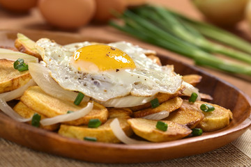 Fried egg on crispy fried potato slices with fried onion