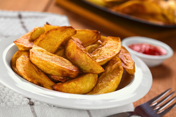 Fresh homemade crispy fried potato wedges on plate