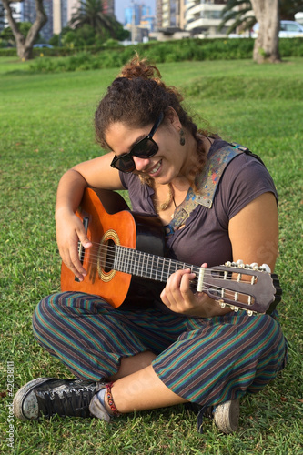 Beautiful smiling Peruvian woman playing the guitar