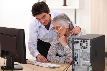 Young man showing grandmother computer