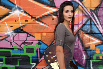 Girl with guitar in front of painted wall