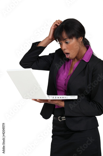 Businesswoman staring in shock at her laptop