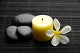 spa stones, candles and tropical frangipani flower on bamboo mat