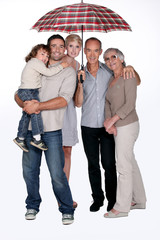 Family standing under umbrella
