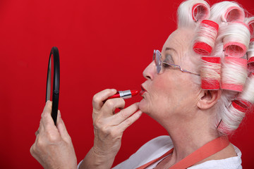 Woman with curlers putting on lipstick