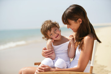 Mother and daughter sat on chair at the beach