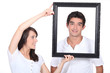 Couple stood with empty picture frame