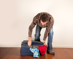 man closing his overfull suitcase