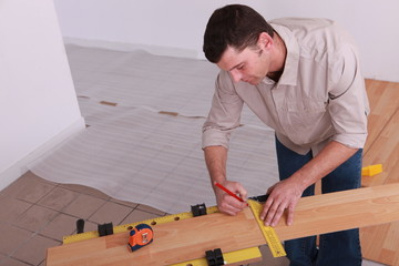 Man measuring plank of laminate flooring