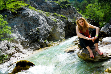 Girl sits on a stone by clean river in the Austrian Alps