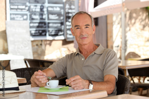 Man drinking coffee outside a cafe