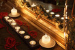 Burning candles and long red beads lie near mirror