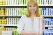 Blonde girl wearing white shirt keeps yoghurt in shop