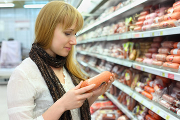 Blonde girl wearing scarf chooses sausage in large store