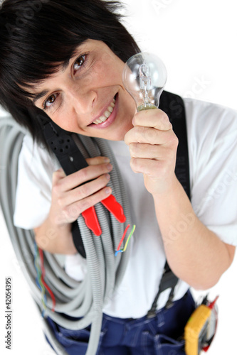Playful female electrician holding replacement light bulb