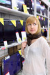 Blonde girl wearing scarf thinks about buying TV in supermarket;
