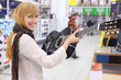 Happy girl wearing scarf holds guitar in supermarket