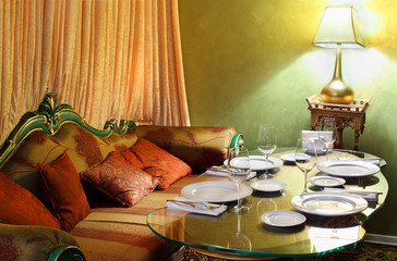 beautiful glass table with serving, lamp and sofa