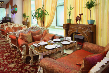 eastern interior of beautiful restaurant, carved sofas and table